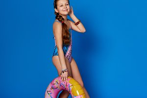 Attractive girl teenager 10 years in swimsuit,inflatable ring.Pretty little lady smile isolated blue background studio.Fashion girl model poses full-length.Concept holiday summer vacation, travel.