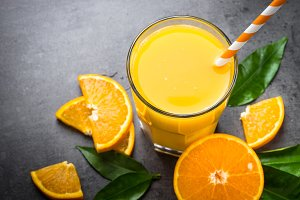 Orange juice in glass on black.