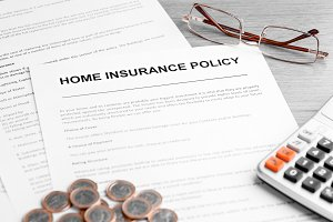 Home Insurance Policy. Calculator, Glasses and Euro Coins on Table