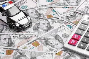 Close-up of a Police Car Model with Calculator on Dollar Notes