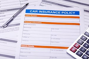 Car Insurance Policy. Documents, Pen and Calculator on Table