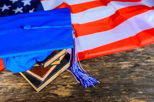 blue graduation hat on books US flag