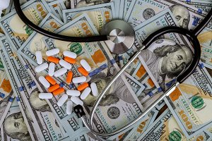 Pills and stethoscope on US dollar