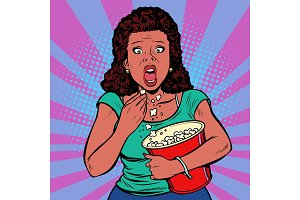 Woman watching a scary movie and eating popcorn