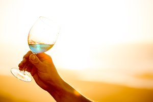 Mens hand holding glass of spanish blue with wine on sea ocean background