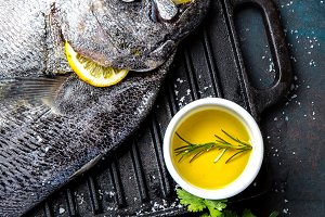Food background with raw fresh fish reineta, herbs, olil and lemon. Top view