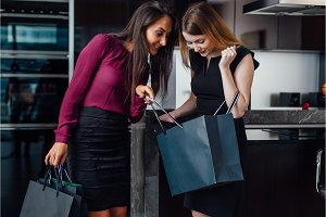 Two gorgeous women after shopping at home. A girl showing her purchases to a female friend standing at home