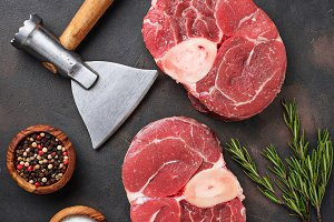 Raw meat osso buco and butchers axe