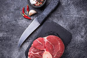 Raw meat osso buco on slate cutting board