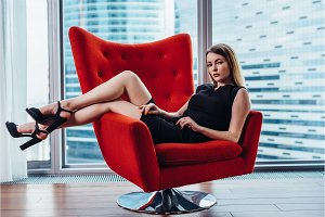 Portrait of sexy businesswoman relaxing in stylish armchair at office