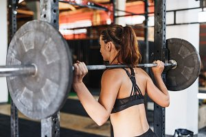 Sportswoman standing with barbell