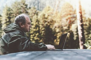 Aged forester man with netbook