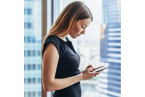 Confident young female using apps on mobile phone standing near big window in modern office