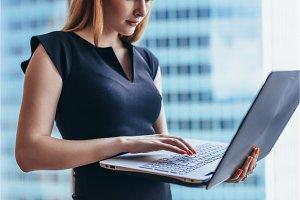 Close-up view of female worker holding laptop writing email in office building