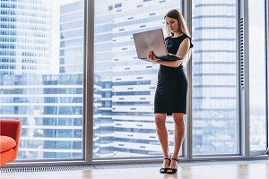 Businesswoman holding laptop standing in modern office against window with city view