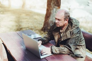 Man using laptop outdoors, forest