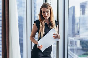 Portrait of pretty young woman holding documents looking at camera standing in office