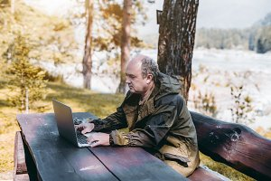 Man with laptop in forest near river