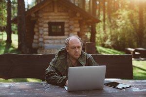 Adult gamekeeper works on laptop