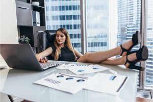 Woman sitting at desk with legs on table working on laptop analyzing financial statistics of the company
