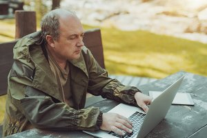 Portrait of man with laptop outdoors