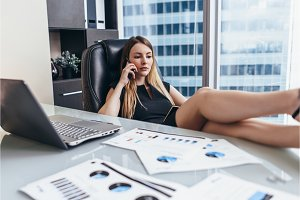 Confident female chief executive talking on phone while sitting with her feet on desk at work