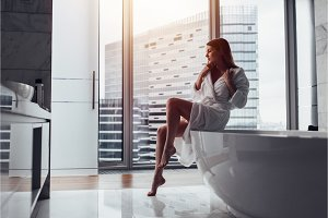 Back view of young woman wearing white bathrobe standing in bathroom looking out the window with bathtub in foreground