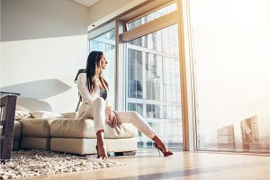 Woman sitting on a sofa at modern apartment