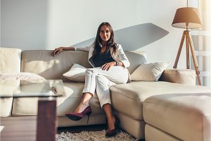 Portrait of businesswoman sitting on sofa relaxing after work at home