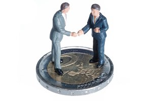 Two miniature businessmen on a coin
