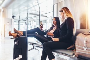 Two successful women resting in arrival hall waiting for a transfer sitting with their legs on suitcase surfing the internet using mobile phone at airport