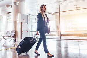 Elegant young woman walking and pulling her suitcase in the airport terminal