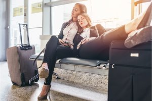 Two tired female tourists sleeping sitting on bench with baggage near them in waiting room in airport