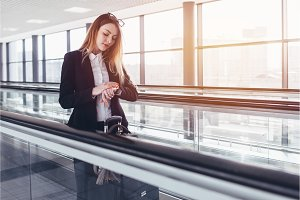Young businesswoman standing on moving walkway and looking at her wrist watch in airport
