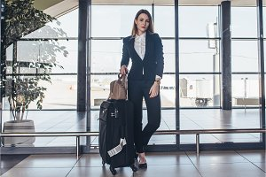 Full-length portrait of confident young business traveler wearing formal suit standing with heavy roll-aboard suitcase in airport terminal