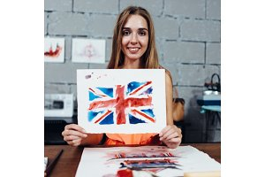 Smiling female artist showing her works, British flag drawn with watercolor technique