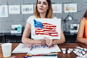Smiling female artist showing her works, American flag drawn with watercolor technique