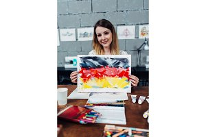 Creative young female designer holding a painting of German flag showing a new print idea sitting at stylish workshop