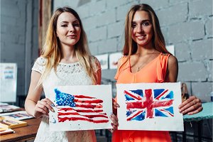 Close-up image of two young women holding a drawing of British and American flags hand-drawn with aquarelle technique on plain paper