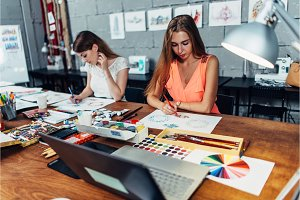 Designers workspace. Two female artists drawing decorative elements sitting at desk in creative studio