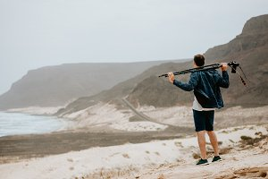 Photographer with camera looking for motive of unique landscape. Sand dunes and volcanic cliffs on the Atlantic coastline. Baia Das Gatas, near Calhau, Sao Vicente Island Cape Verde