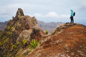 Traveler with backpack looking over the mountain peaks. Stunning arid landscape of Santo Antao island, Cabo Verde