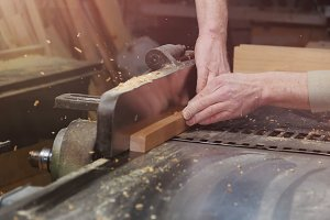 Carpenter Working on Woodworking Machines in Carpentry Shop. Male Hand Close up.