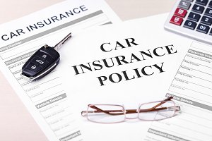 Car Insurance Policy. Document, Key, Glasses and Calculator on Table