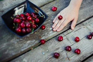 Child's hand with a cherry