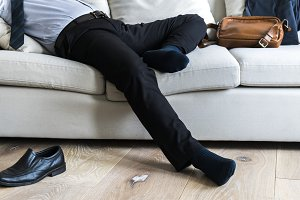 Asian businessman laying on couch