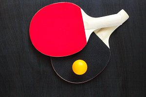Two table tennis or ping pong rackets and ball on a black background