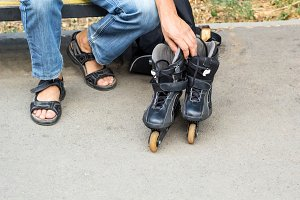 Closeup of man guy putting on roller skates outdoor