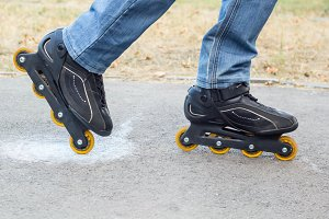 Young man in blue jeans riding roller skates in the city. Close up legs