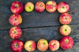 Apples on wooden table background. Fresh fruit backdrop with empty space for text